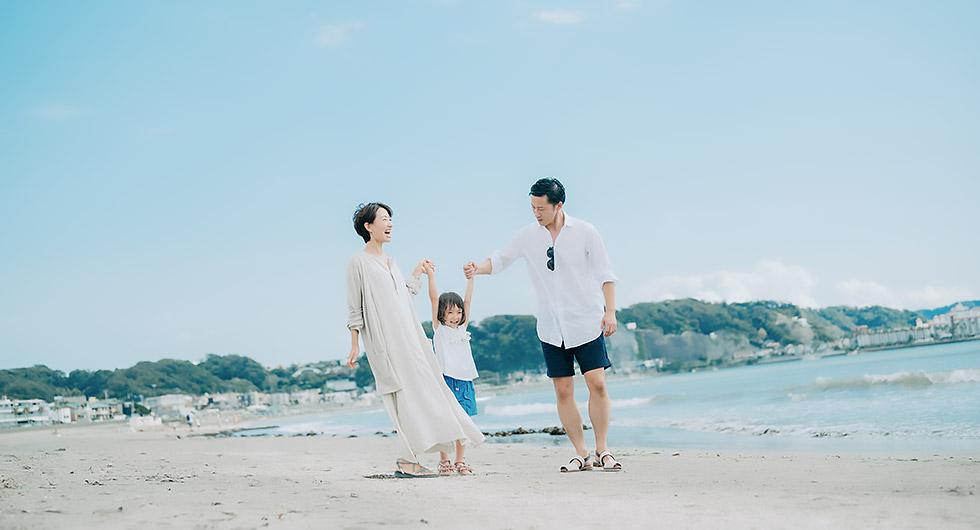 幼稚園くらいの子供と夫婦が海岸で散歩している楽しげなようす