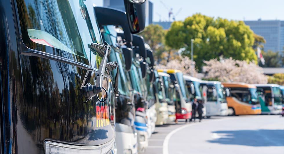国内の春のお花見シーズンに観光バスが駐車場に横一列にずらりと並んだようす